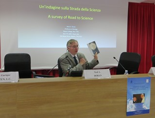 Neal Doran showing the book The Road of Science and the Ways to God that is dealt with in his intervention.